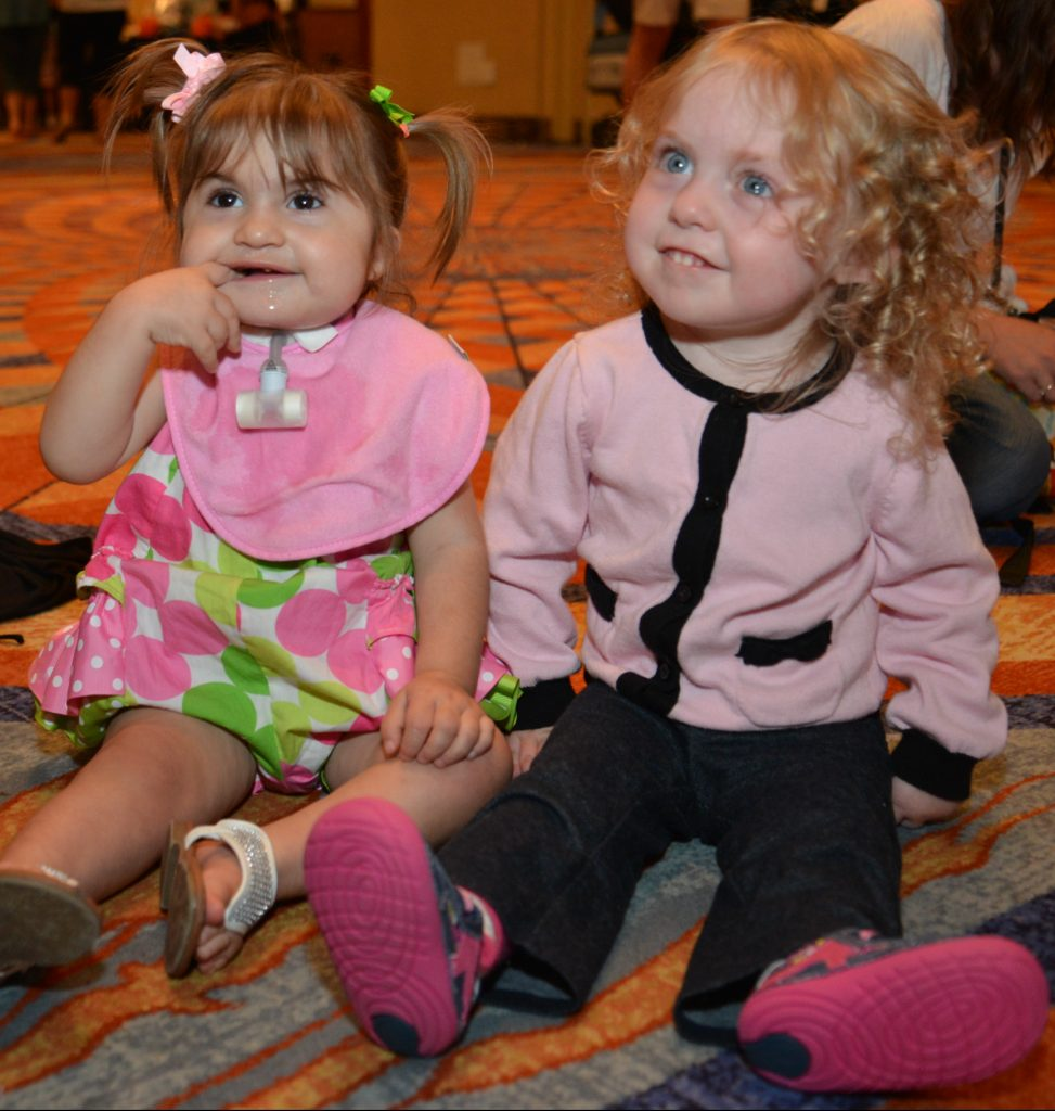 two little girls sitting on a carpet, one girl has a trach and is biting her finger.