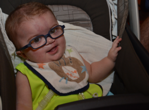 Little boy with glasses sits in a stroller
