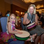 a young girl with CHARGE plays a drum along with a partner