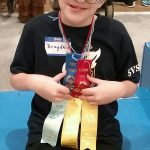 Brayden, holding his Special Olympics awards