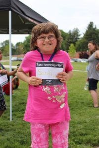 a young girl with charge holding her race bib celebrates her run