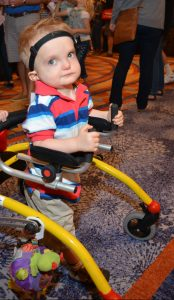 A young boy with CHARGE uses a walker to walk on a carpet