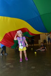 Camp photo of young girl standing beneath a parachute