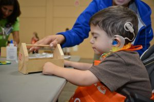 Young boy wearing a cochlear implant works on a project at camp